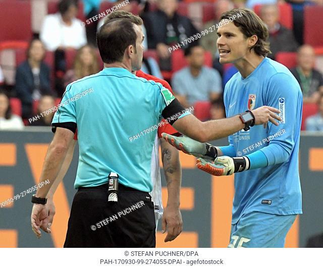 Augsburg goalie Marwin Hitz (r) complains to referee Marci Fritz during the German Bundesliga football match between FC Augsburg and Borussia Dortmund in...