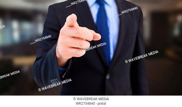Business man mid section pointing in blurry room