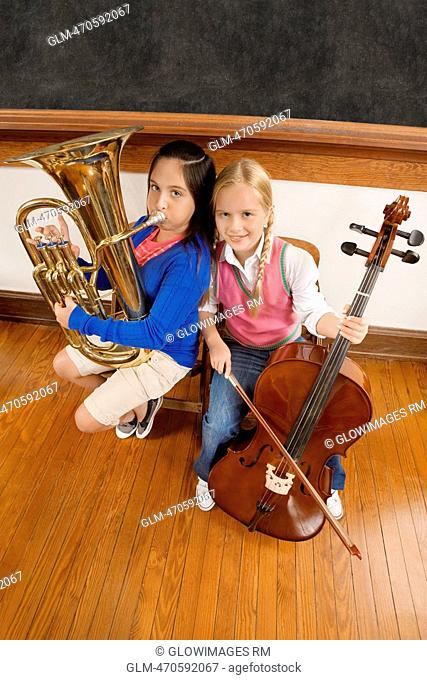 Two schoolgirls playing a cello and a tuba in a classroom