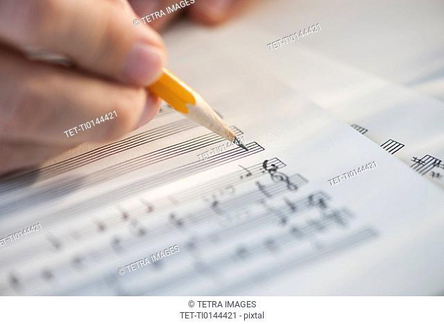 Man writing notes on sheet music