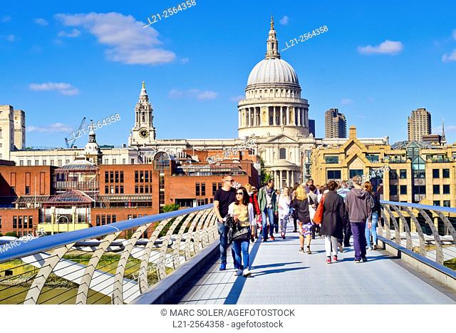 People walking along the Millenium Bridge with St Paul's Cathedral behind. London, England, United Kingdom