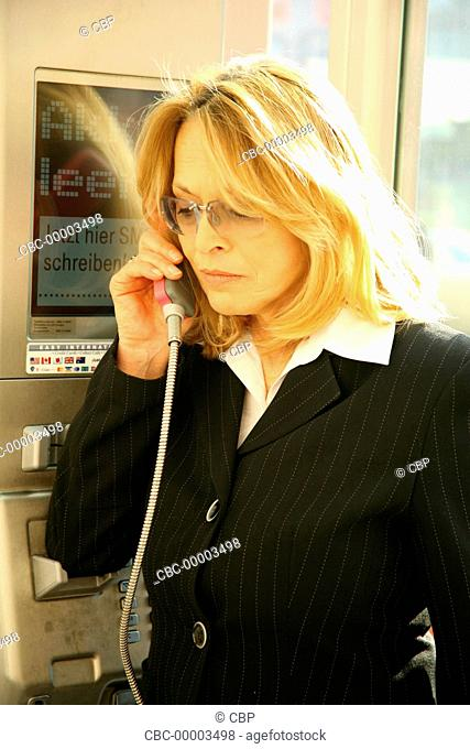 Mature Woman Using A Payphone