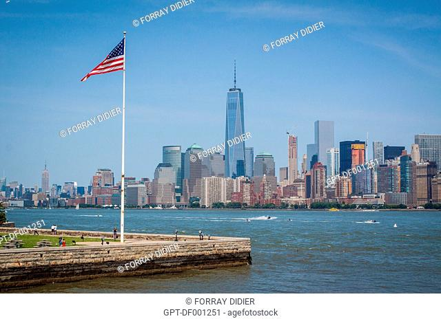 AMERICAN FLAG FLYING OVER ELLIS ISLAND ACROSS FROM THE MANHATTAN SKYLINE WITH ONE WORLD TRADE CENTER AND THE EMPIRE STATE BUILDING IN THE BACKGROUND
