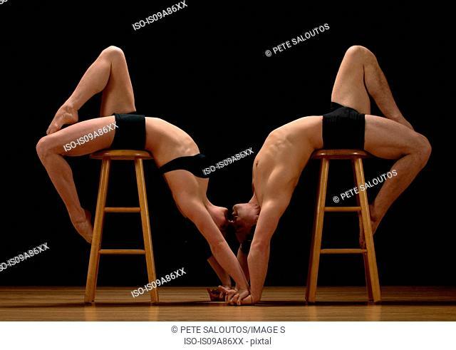 Mid adult dancers bending over stools against black background
