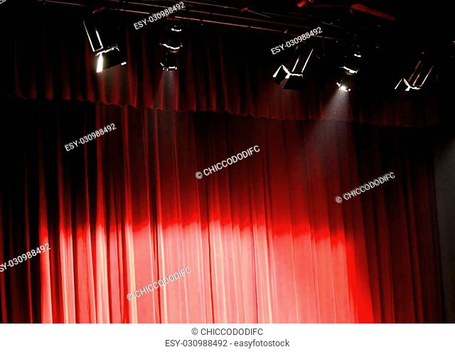 red theater curtain over the stage and the spotlights projectors