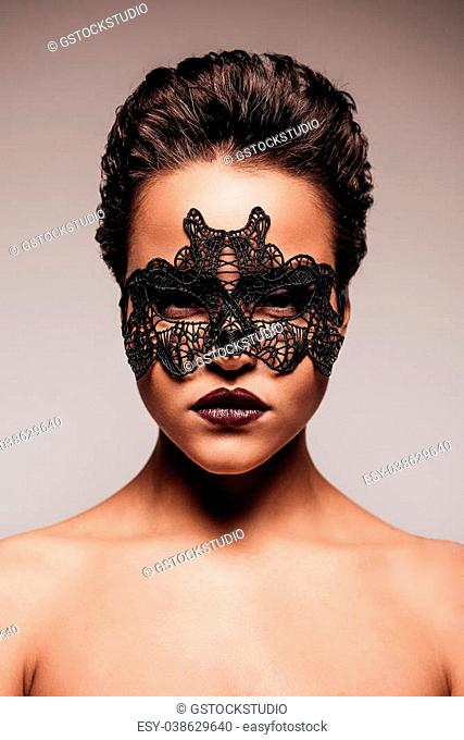 Beauty in mask. Portrait of beautiful young shirtless woman in black mask looking at camera while standing against grey background