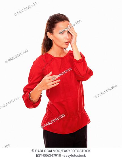 Portrait of young latin woman on red blouse with headache looking at you while standing on isolated studio