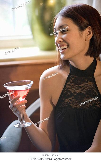 Portrait of young adult woman holding a drink and sitting inside a restaurant