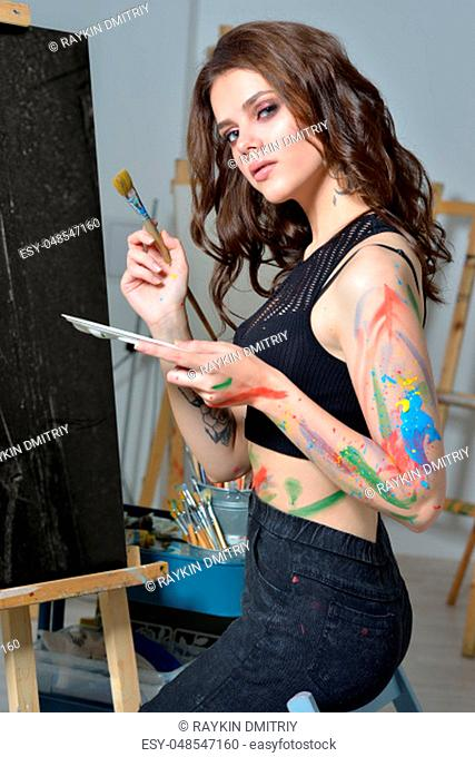Portrait of the beatiful woman with brushes painting at art studio