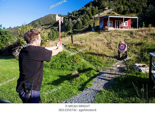 A Man Takes An Attempt At An Axe Throw At Blue Duck Lodge, In Whanganui National Park; Whakahoro, New Zealand