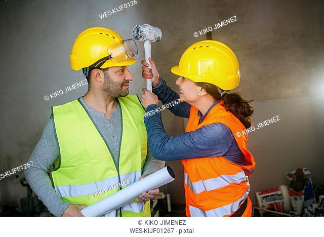 Playful man and woman fighting on a construction site