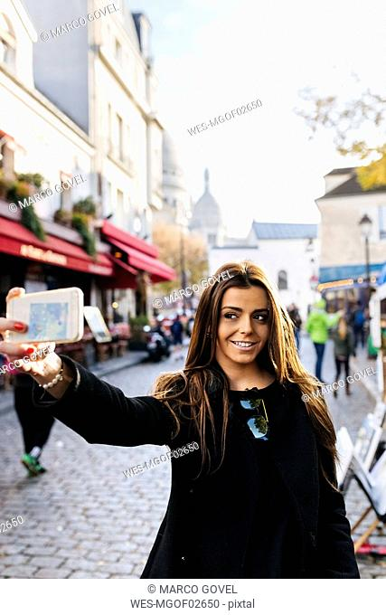 France, Paris, young woman taking a selfie in Montmartre
