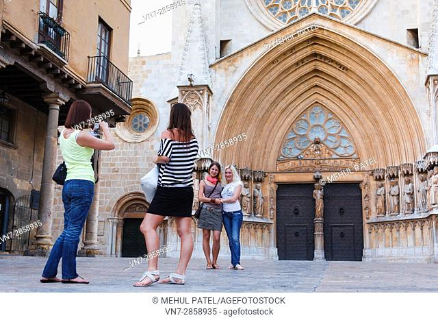 Tourists posing in front of the main facade of Tarragona Cathedral, Catalonia, Spain