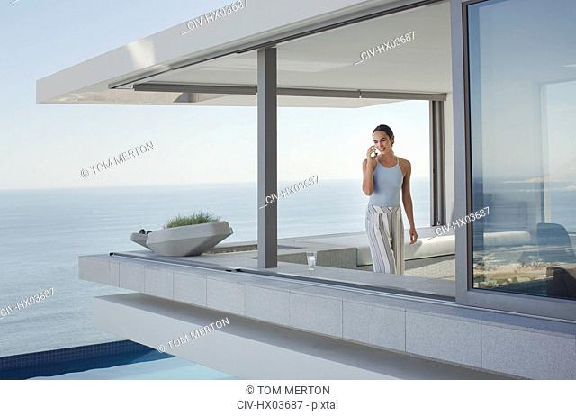 Woman talking on cell phone on modern, luxury home showcase exterior patio with ocean view