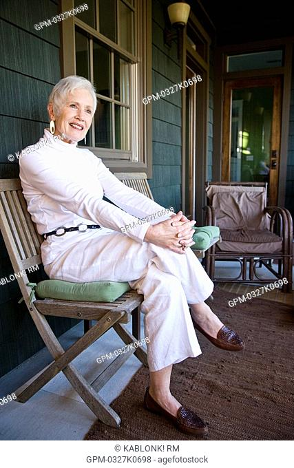 Senior woman sitting in chair on front porch