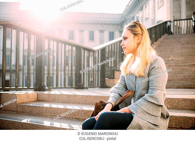 Young woman sitting on city stairway looking away, Milan, Italy