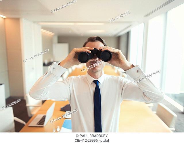 Portrait of businessman using binoculars in conference room
