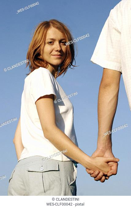 Young couple holding hands outdoors, smiling, low angle view