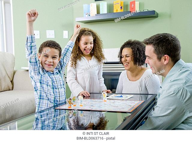 Mixed race family playing board game