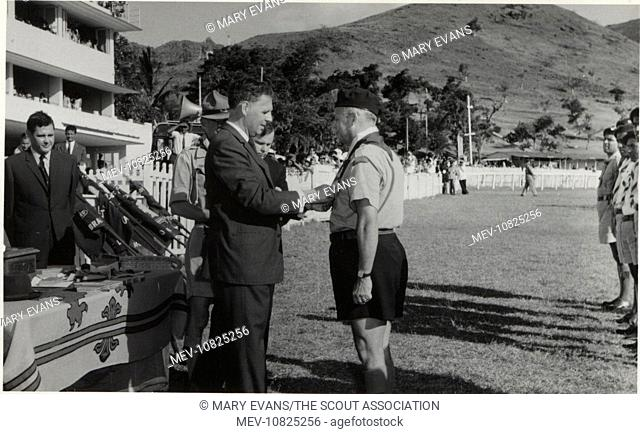 The Governor of Mauritius, Sir John Shaw Rennie (1917-2002), presenting scouting leader Guy de la Hogue with the Silver Acorn at a rally