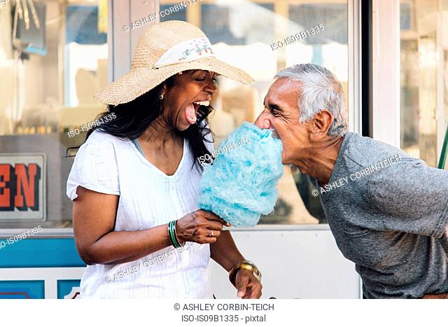 Senior couple eating cotton candy, laughing, Long Beach, California, USA