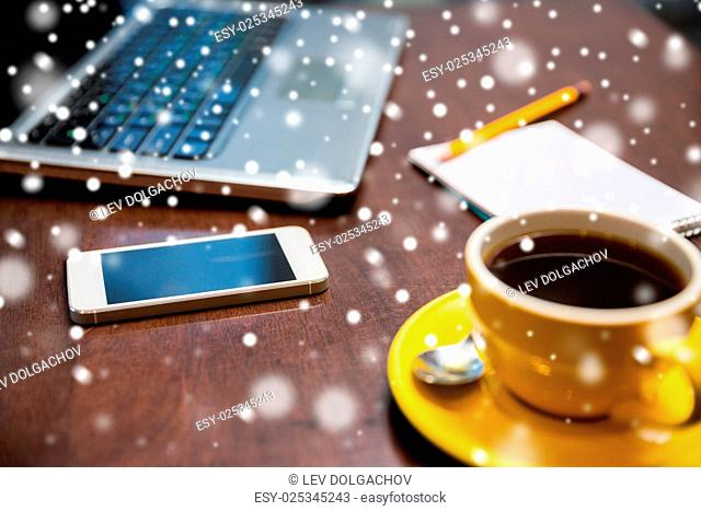 business, education, technology and object concept - close up of smartphone, coffee cup and laptop on table over snow