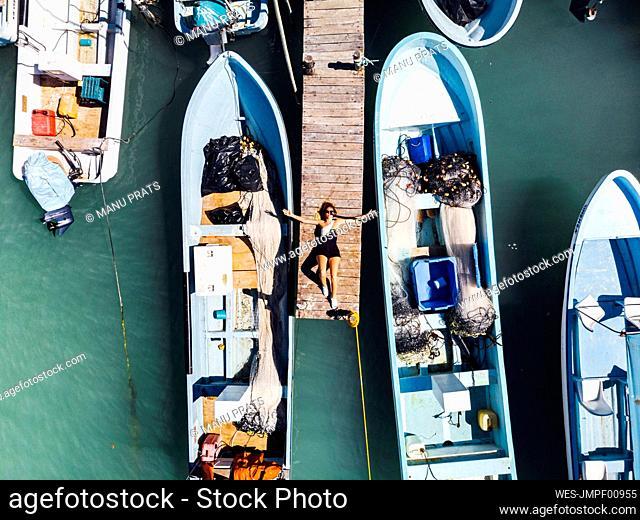 Woman lying on jetty amidst boats in Rio Lagartos, Yucatan, Mexico