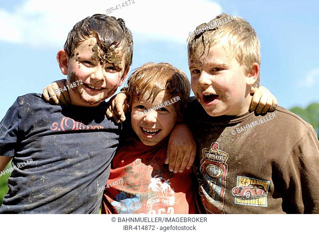 Three friends boys covered with mud and having fun