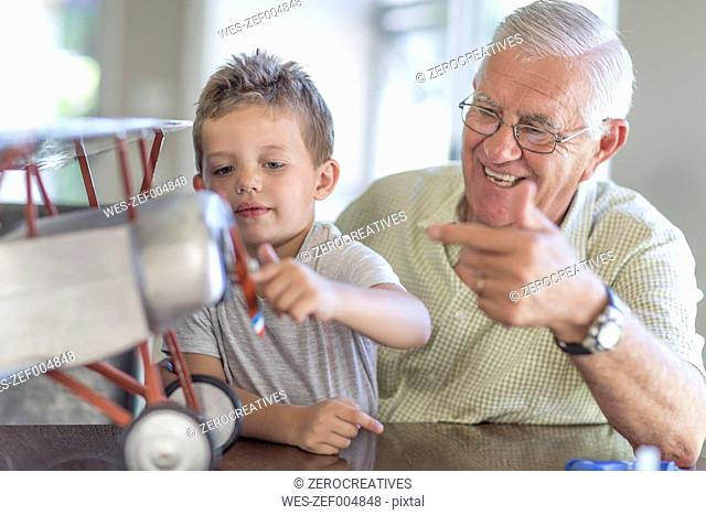 Grandfather and grandson building up a model airplane