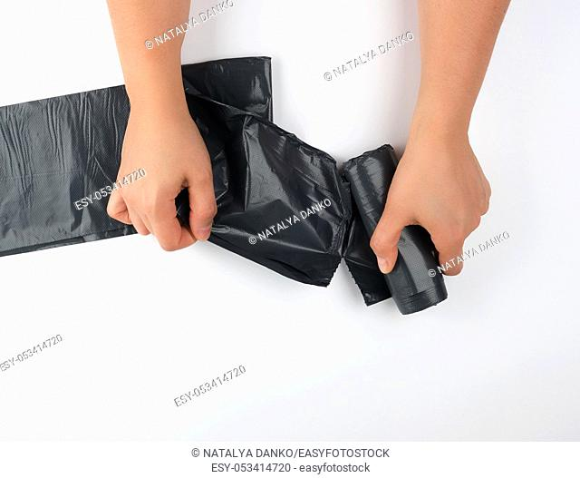 female hands tear off a black bag for a bin from a roll, white background, top view