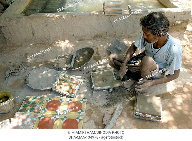 Man making Athangudi tiles which are not ceramic quite heavy and costly ; Tamil Nadu ; India