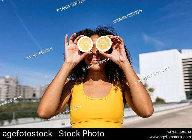 Portrait of laughing young woman covering eyes with lemon halves