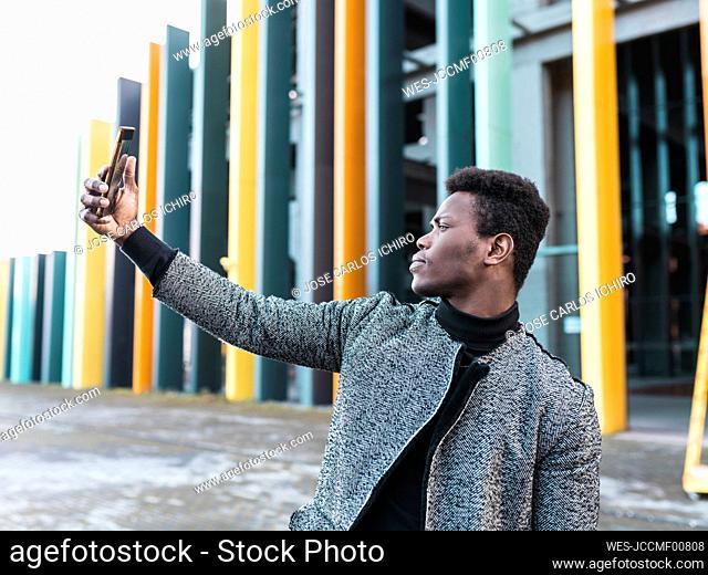 Portrait of elegant young man using phone