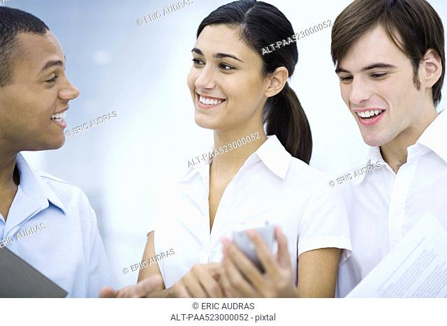 Young woman showing male colleagues her cell phone, smiling