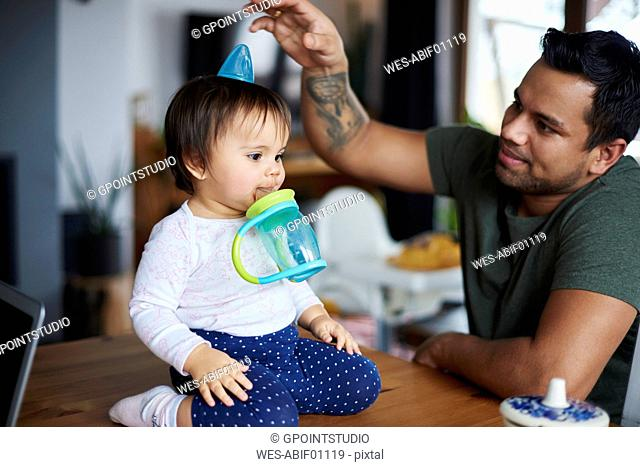 Playful father having fun with his baby sitting on table at home