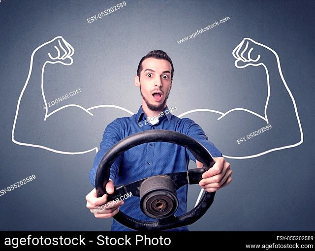 Young man holding black steering wheel with muscly arms drawn next to him
