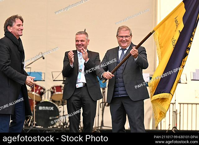 17 October 2021, Baden-Wuerttemberg, Ìberlingen Am Bodensee: Joachim Schuster (r), Mayor of Neuenburg am Rhein, holds the flag of the State Horticultural Show