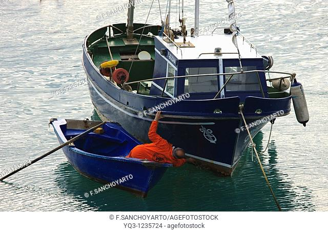 Fisherman cleaning his boat's hull. Port of Castro Urdiales, Cantabria, Spain
