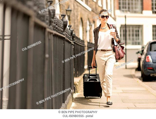 Young businesswoman walking with wheeled suitcase on city street, London, UK