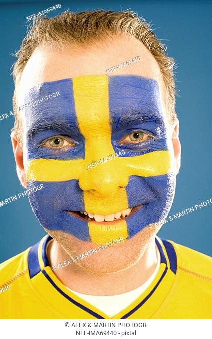 A man with the Swedish flag painted in his face