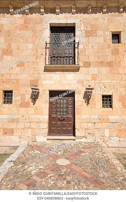 Exterior facade with old wooden door and balcony above, and windows and lanterns, in ancient convent of San Francisco de Asis, from thirteenth century