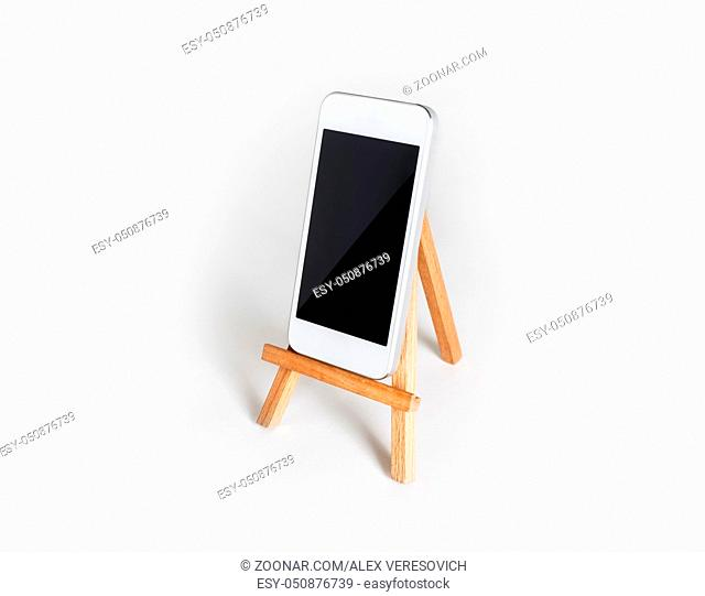 Smartphone with blank screen on wooden stand at white paper background. Mockup for placing your design