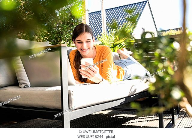 Young woman lying on couch on terrace using cell phone and laptop