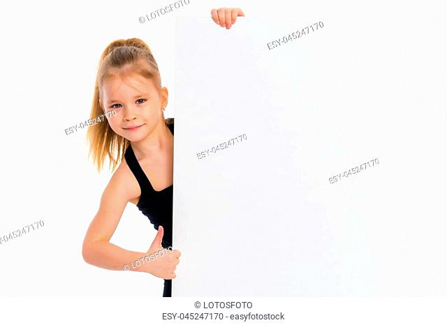 A nice little girl is looking because of an empty banner in which you can insert any text. The concept of a happy childhood, advertising, selling goods