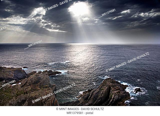 Cabo Sardao coastline in Portugal. Sun streaming through cloud on to the sea