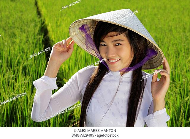 Young woman wearing traditional Vietnamese hat standing in rice paddy