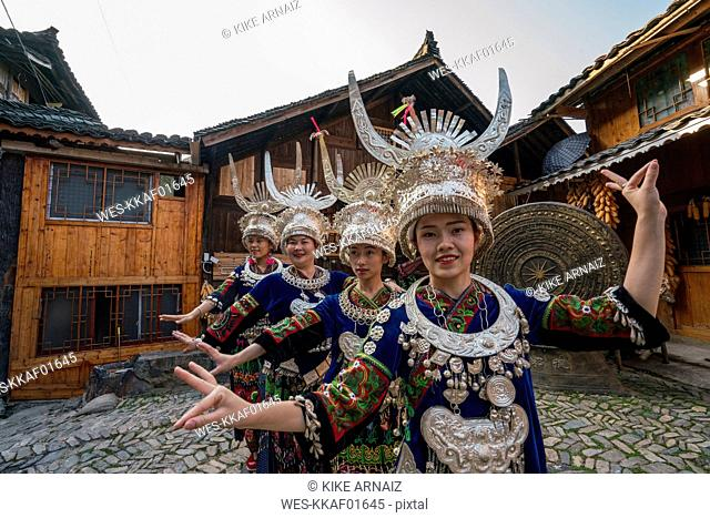 China, Guizhou, Miao women wearing traditional dresses and headdresses posing on village square