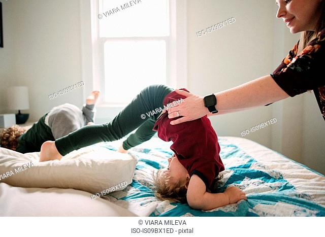 Mother helping son tumble in bed