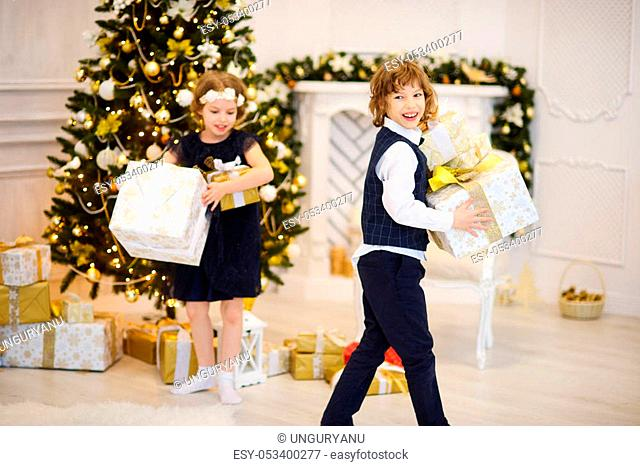 Brother and sister of younger school age stand near the decorated Christmas tree with boxes in hands. To children it is joyful