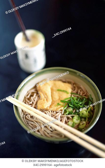 Bowl of Ramen with Soba noodles and tofu and Amazake drink on a table in a Japanese restaurant, Kyoto, Japan